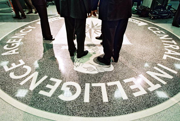 men in suits standing on the seal of the central intelligence agency at headquarters