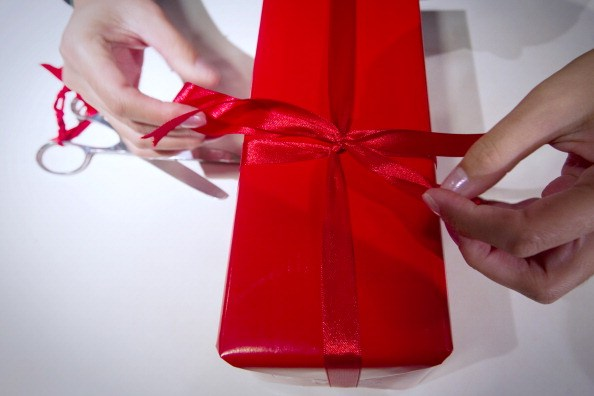 a pair of hands wrap a red present with red ribbon