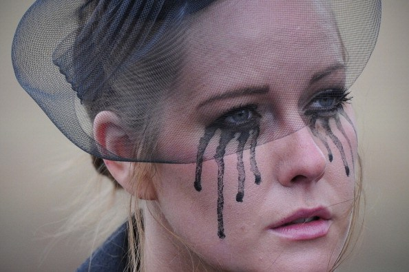 a woman in a black veil with black tear makeup