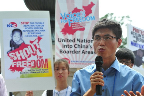 a north korean activist speaks in front of protest posters