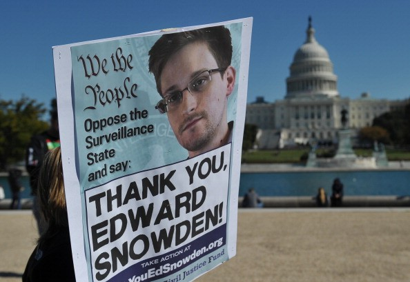 protestors hold a sign protesting mass surveillance outside the US capitol