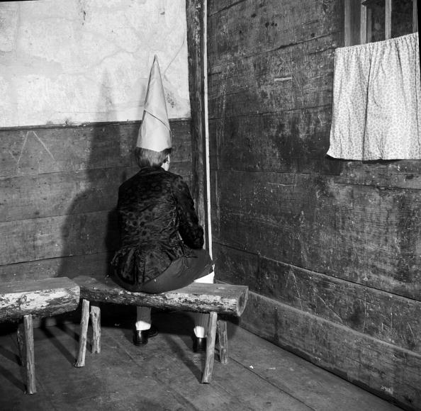 an old black and white photo of a boy in a dunce hat