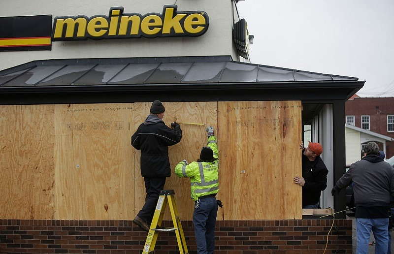 Workers board up windows at a Meineke auto repair shop after demonstrators protesting the shooting death of Michael Brown smashed the windows November 26, 2014 in Ferguson, Missouri. Brown, an 18 year old black male teenager, was fatally shot by Darren Wilson, a white Ferguson Police officer, on August 9, 2014. A St. Louis County 12 member grand jury who reviewed evidence related to the shooting decided not to indict Wilson with charges, sparking riots in Ferguson.