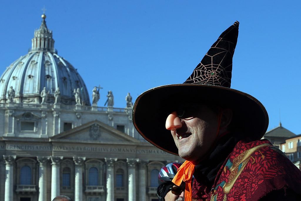 la befana in a pointed black hat walking past the vatican