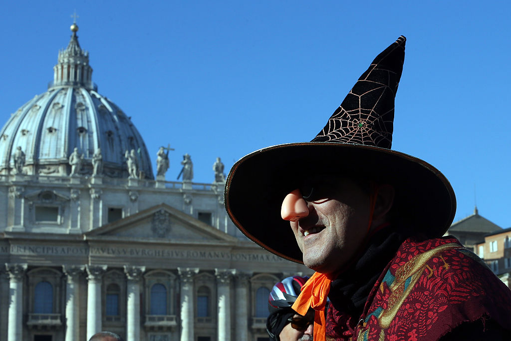 la befana in a pointed black hat walking past the vatican