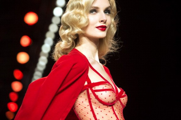 a model in a red negligee and a red cape