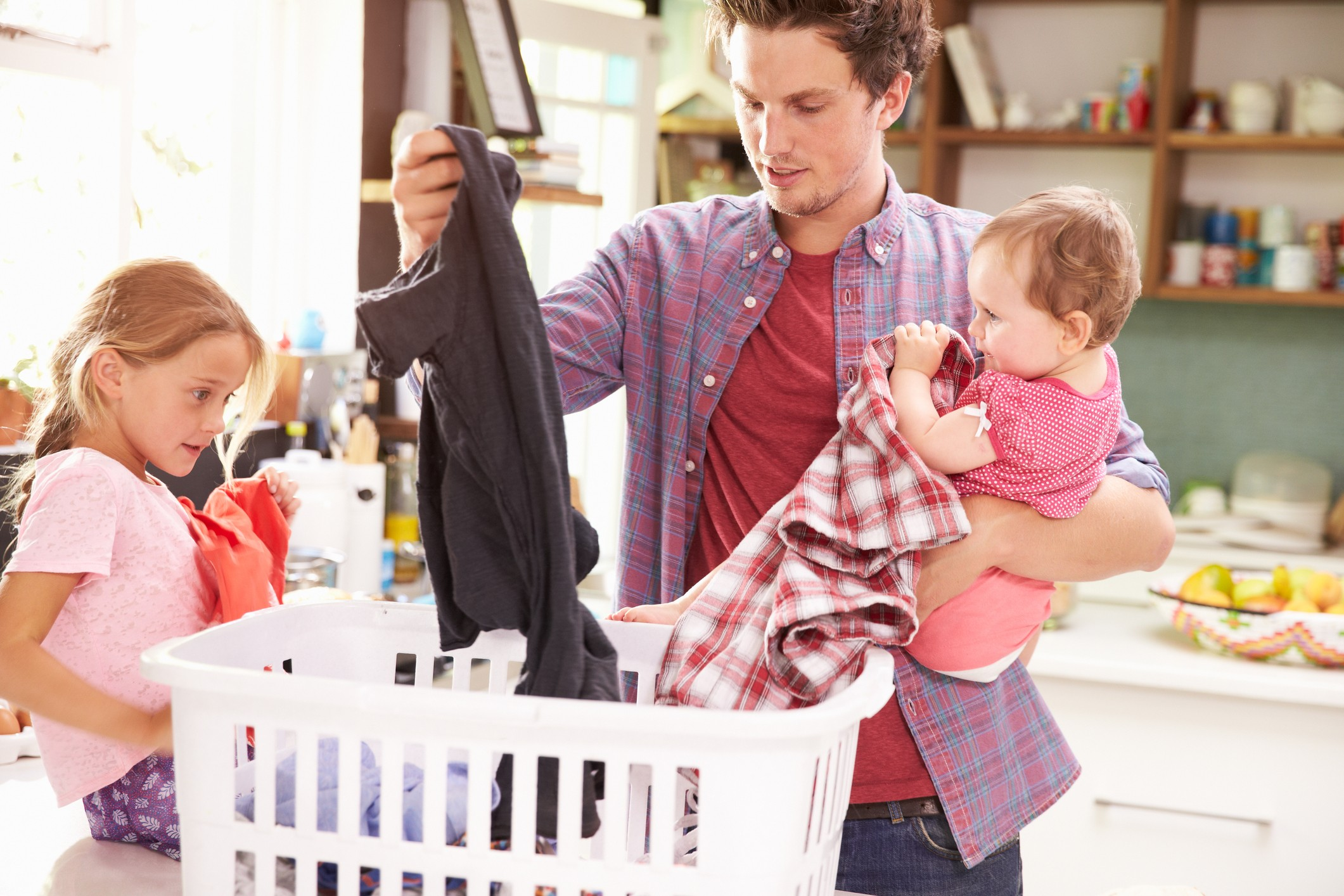 dad and young children sorting laundry