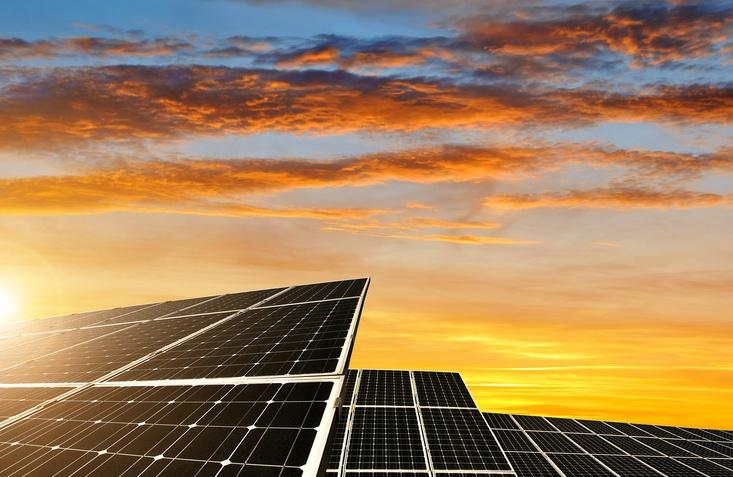 Solar energy panels against sunset sky. Green energy