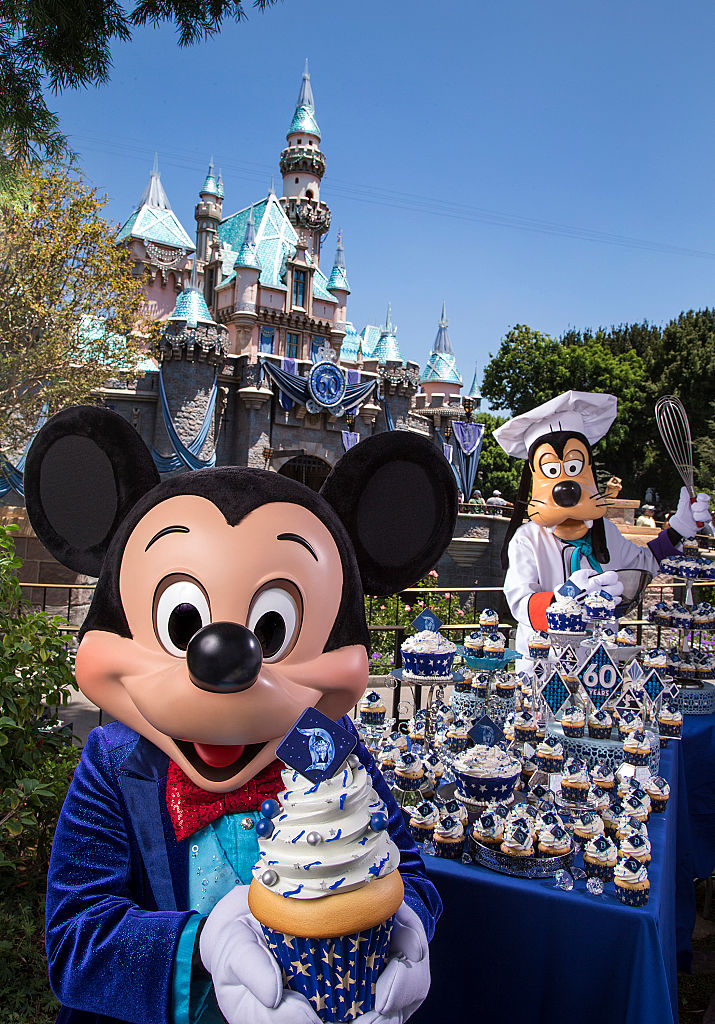 Mickey Mouse and Goofy help prepare celebratory cupcakes at Disneyland.