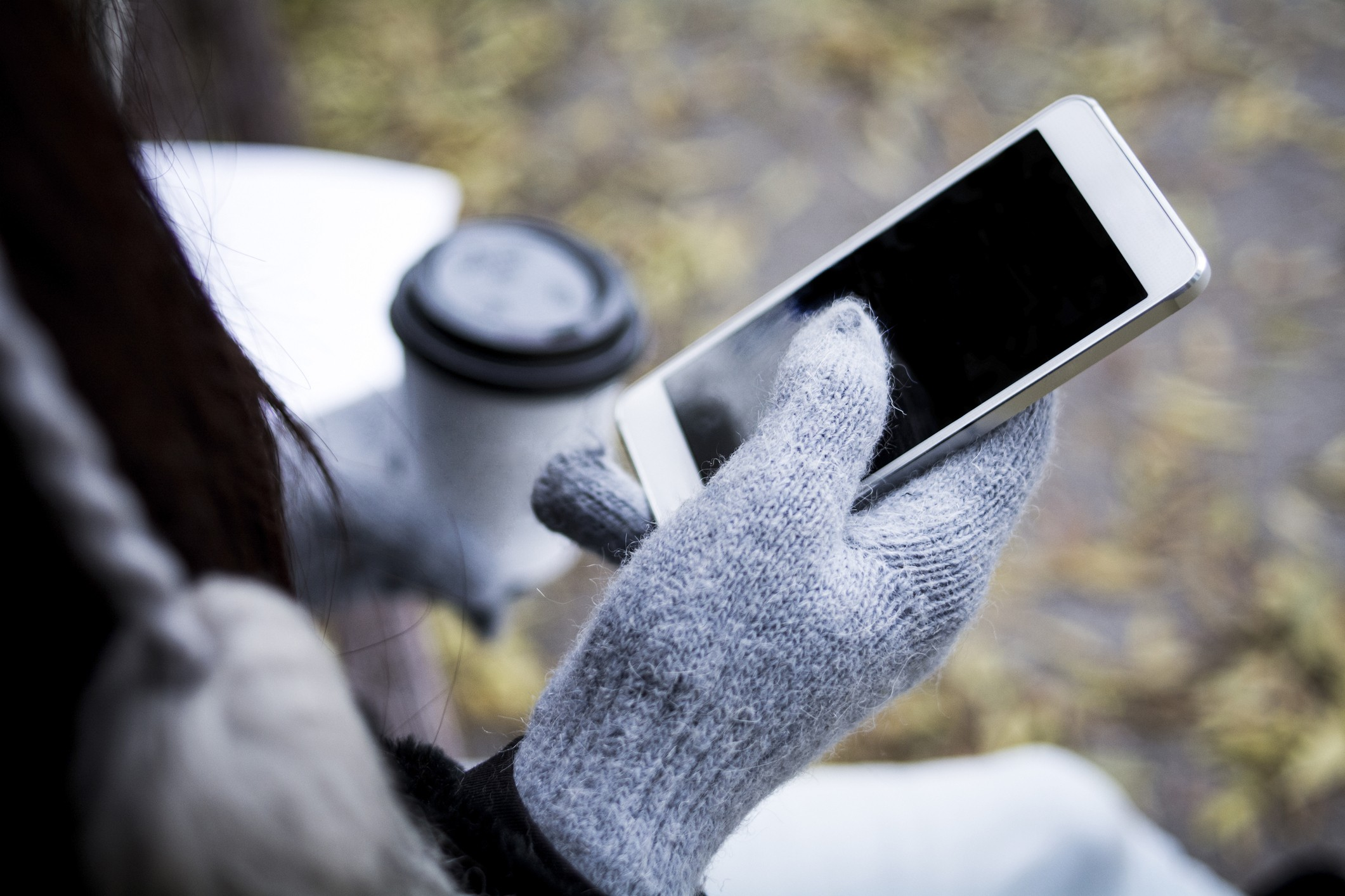 hand wearing glove holding smartphone