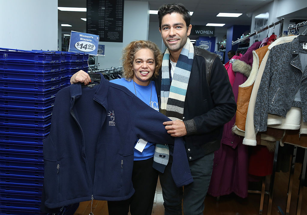 two goodwill employees show off a jacket