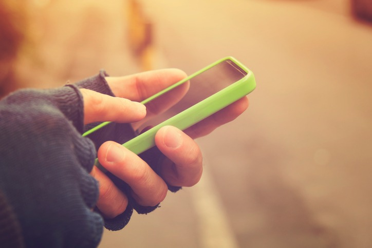 Person with fingerless gloves using their smartphone