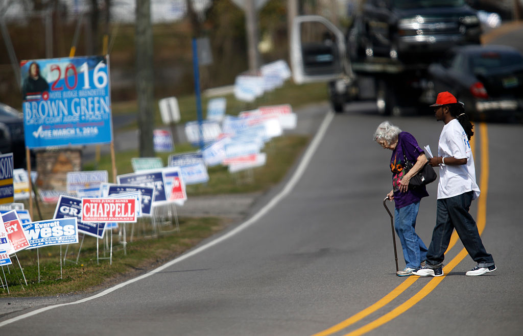 a man helps a woman cross the street to her polling place