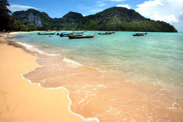 a beach in thailand with long boats and mountains