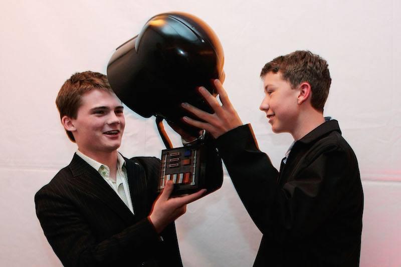 Jake Lloyd posing with a black helmet.