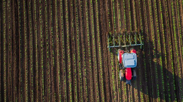 Tractor cultivating field at spring,aerial view.
