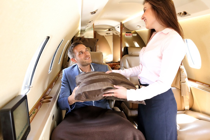 flight attendant handing a pillow to a blanket-covered passenger on an airplane