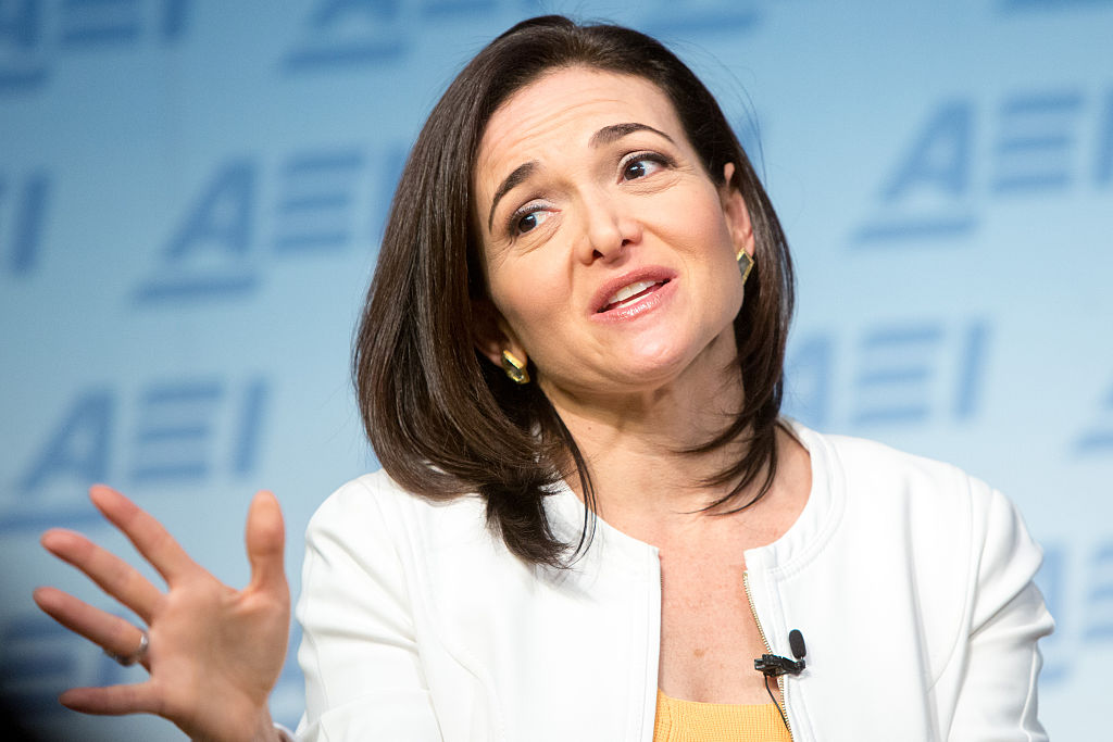 sheryl sandberg in a white blazer speaks against a blue background