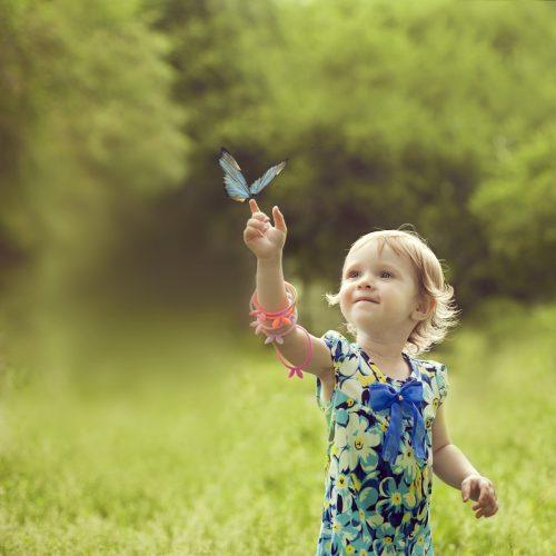 Happy girl sat on the arm of a beautiful butterfly and she enjoys communing with nature