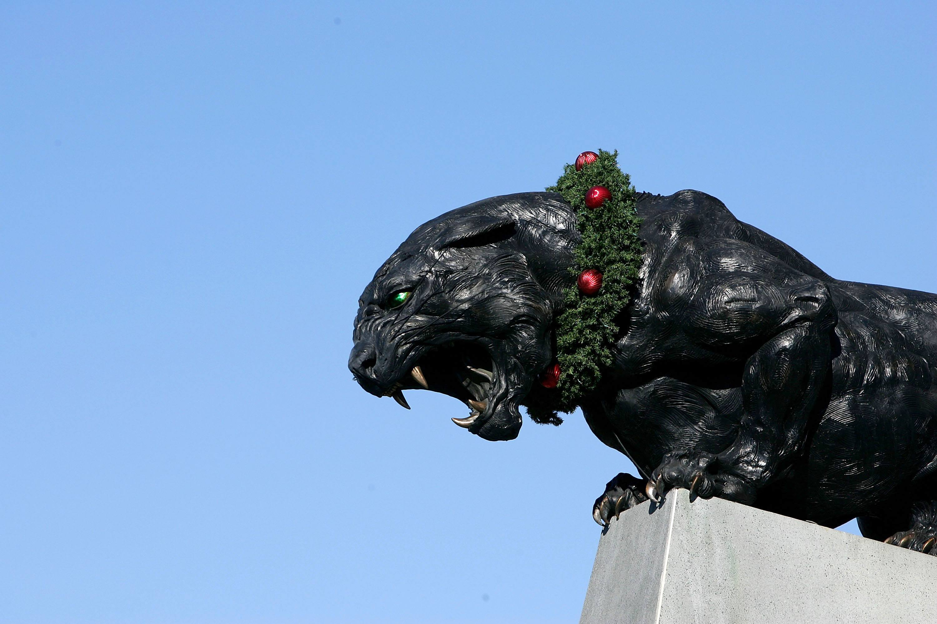 a black panther statue wearing a christmas wreath