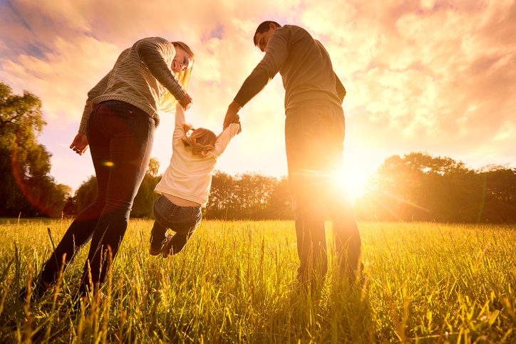 Happy family in the park evening light. The lights of a sun. Mom, dad and baby happy walk at sunset. The concept of a happy family.Parents hold the baby's hands.