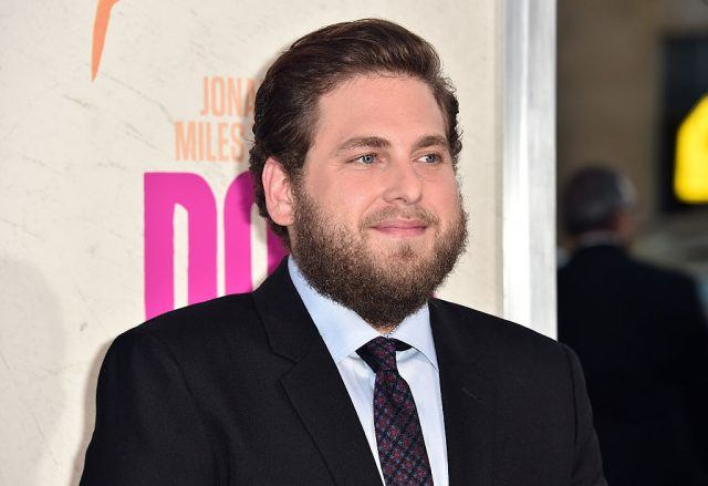 Jonah Hill standing in a black suit and tie.