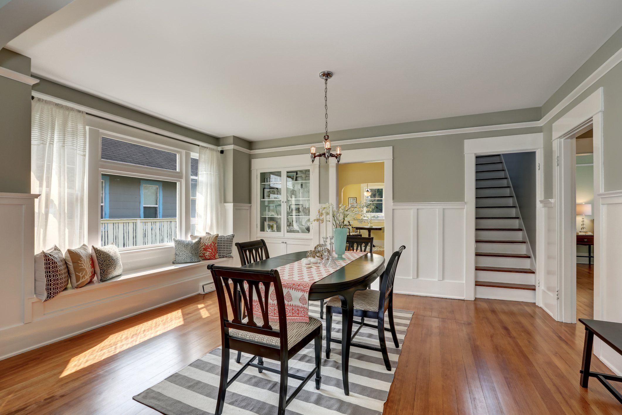 View of a classic dining room with gray walls and medium tone hardwood floors. Glass door cabinet and cozy window seat with pillows