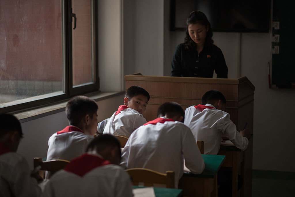 Students of the Pyongyang International Football School sit inside a classroom as they take a test.