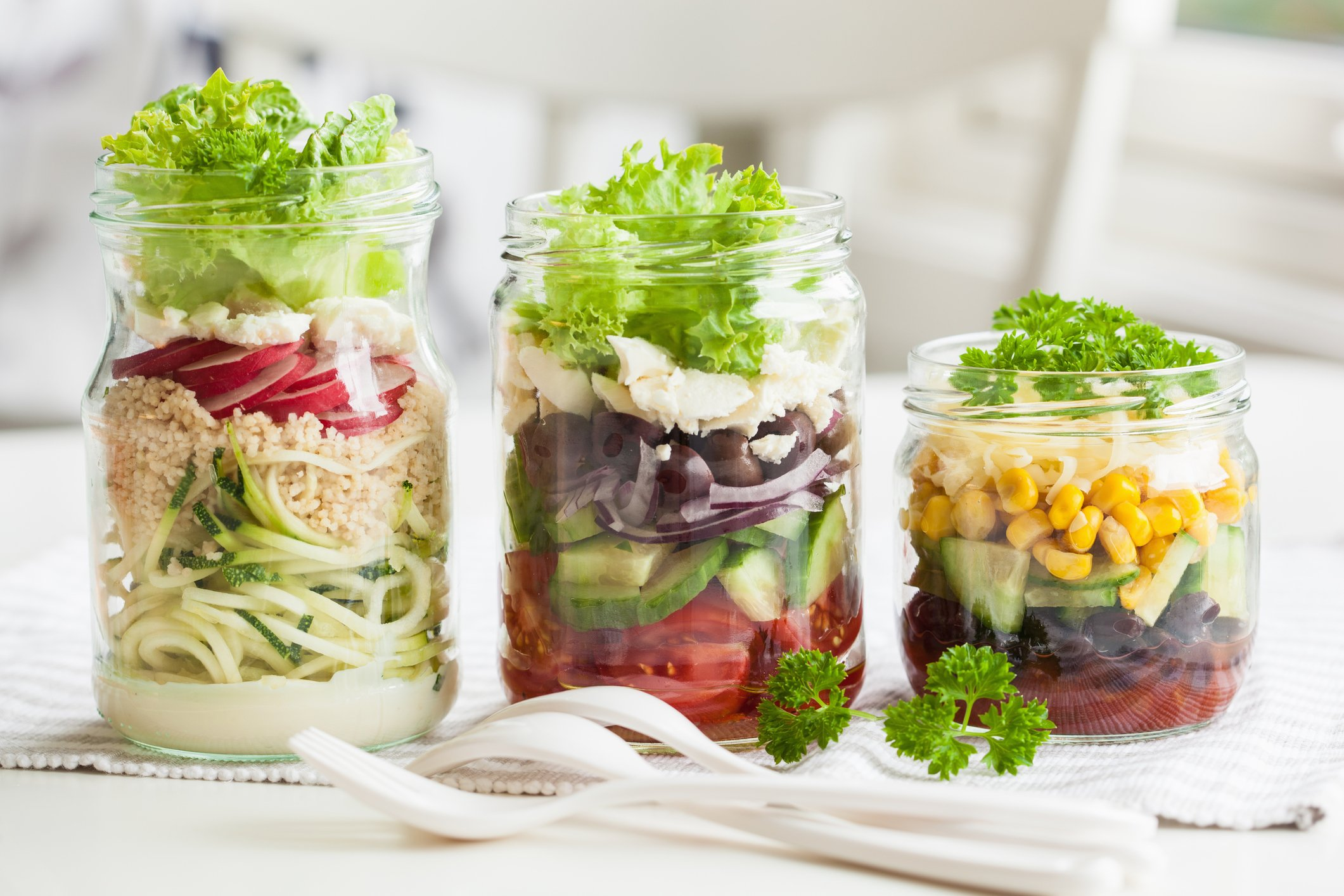 salad in three mason jars