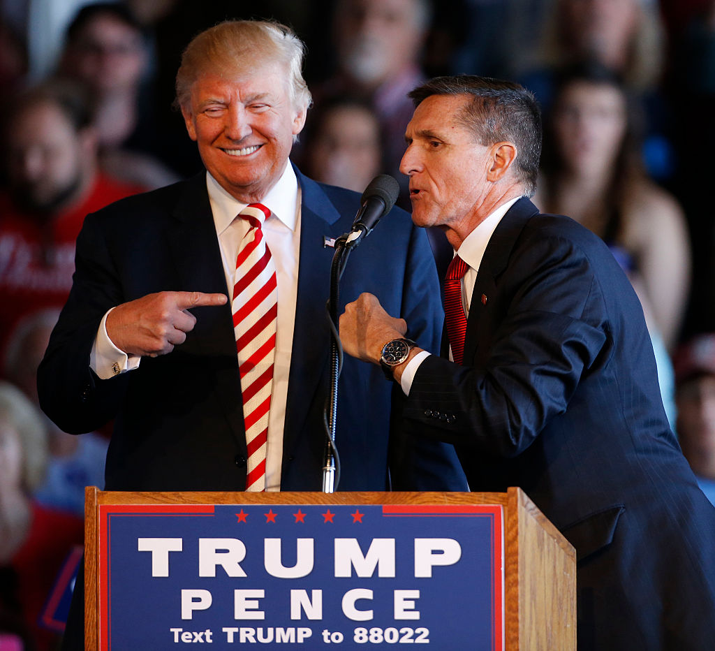 trump and flynn in suits behind a trump campaign sign on a podium