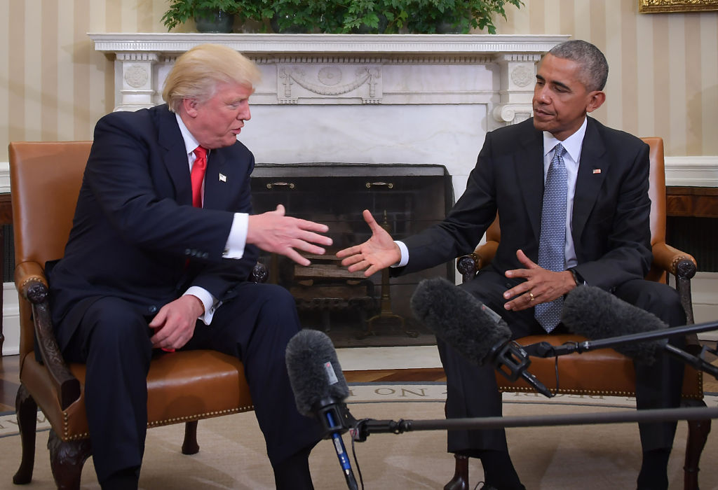 Barack Obama and Donald Trump shake hands in the Oval Office.