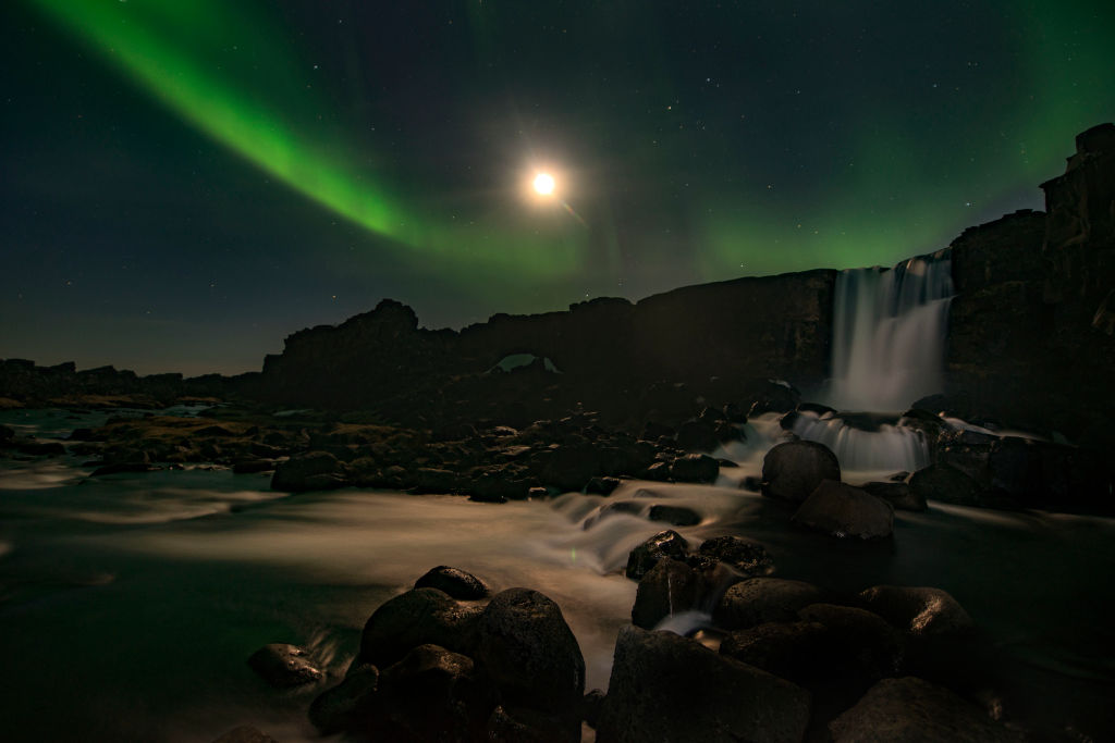 the northern lights above a waterfall at night in iceland