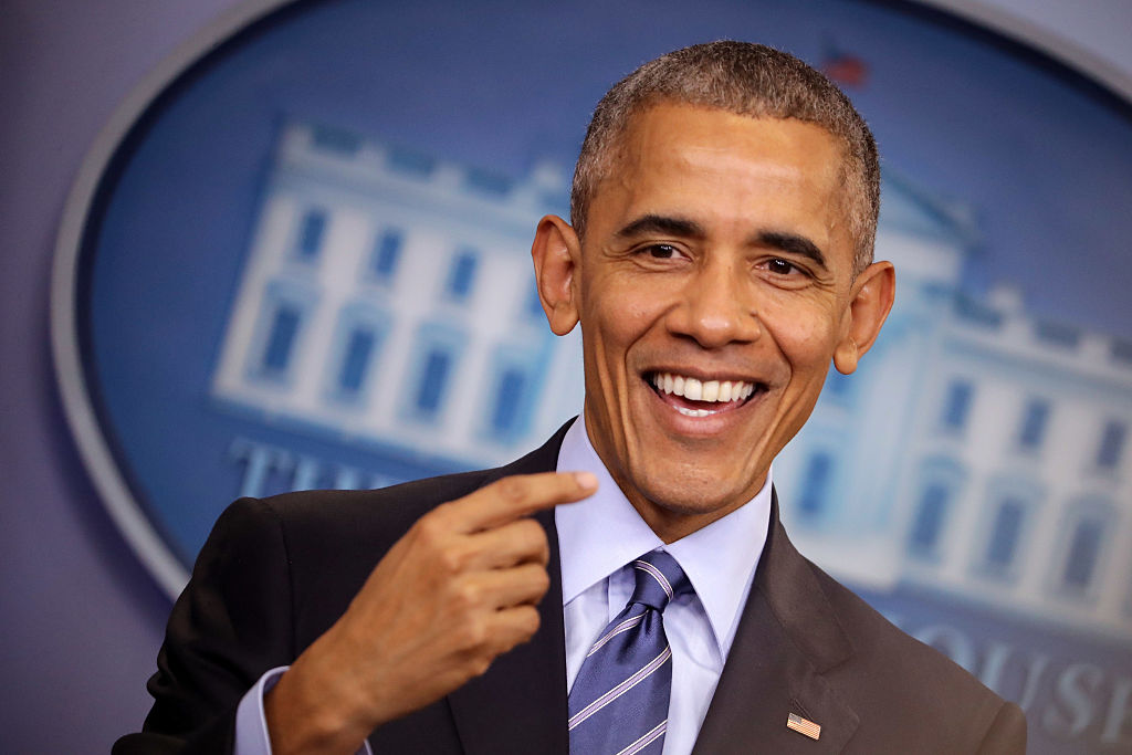 Barack Obama pointing at his own face in a dark suit and blue striped tie