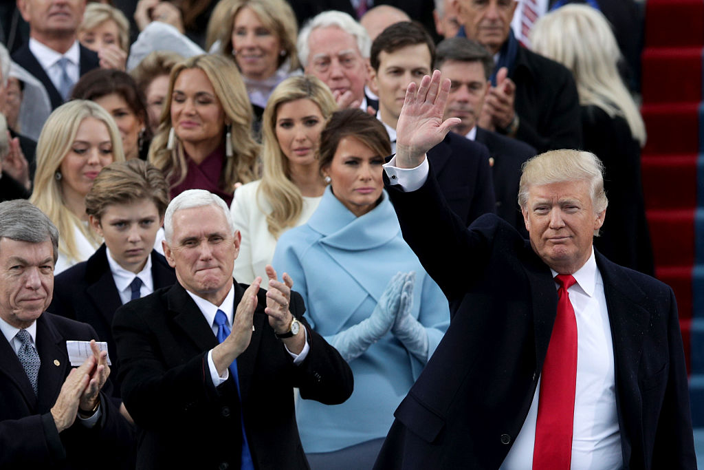 Melania Trump frowning and clapping standing behind Donald Trump as he waves.