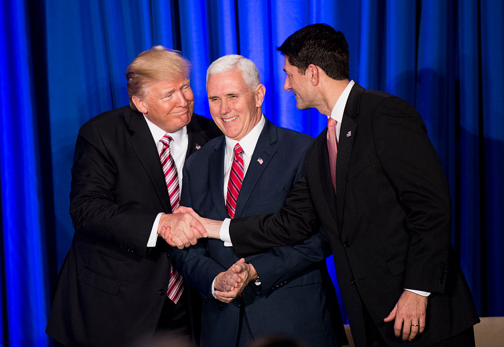 U.S. President Donald Trump shakes hands with Speaker of the House Paul Ryan while Vice President Mike Pence looks on.