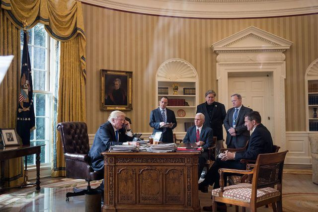 Trump in the oval office surrounded by his cabinet.