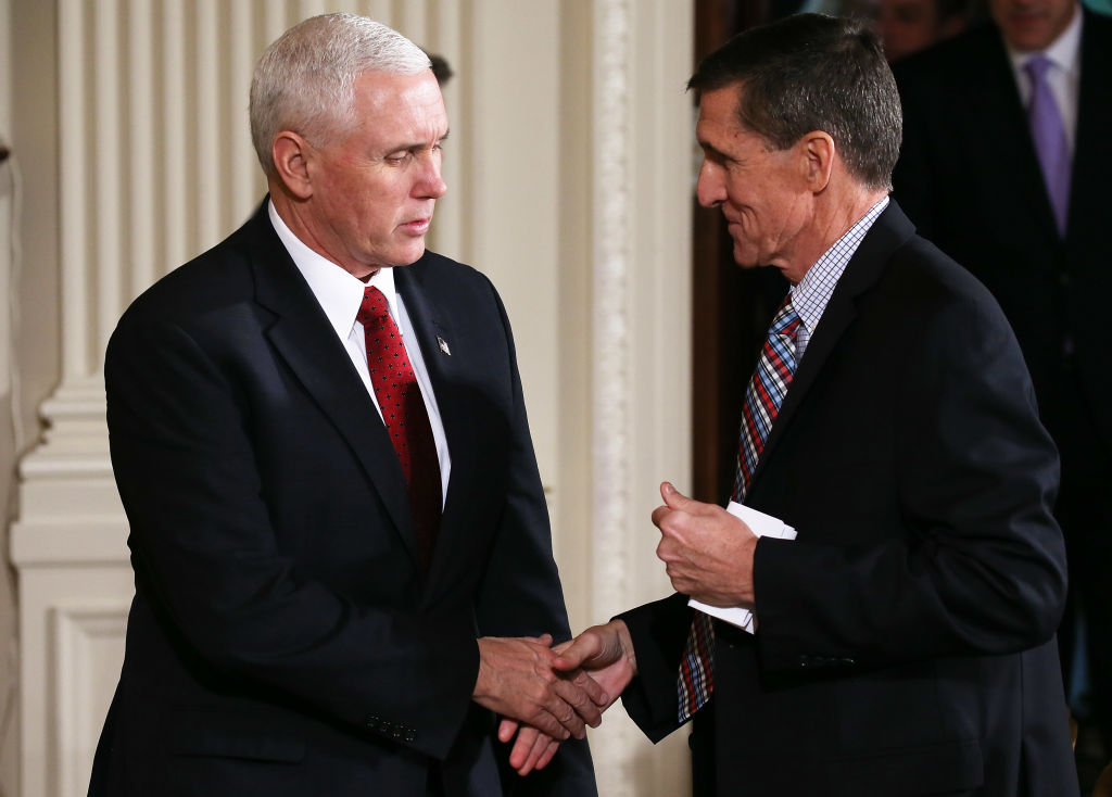 mike pence and michael flynn shake hands against white columns, both in dark suits