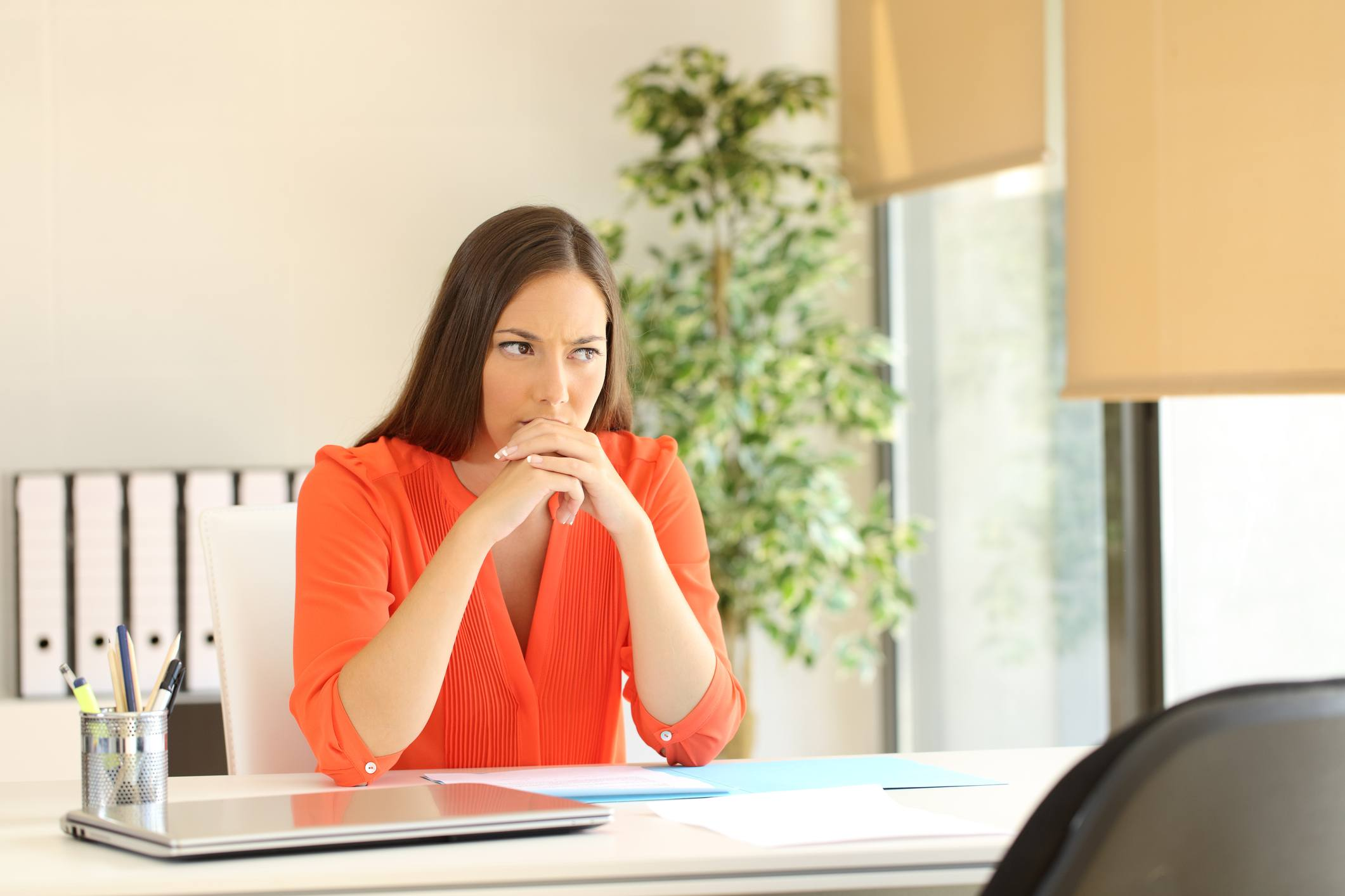 Thoughtful and nervous woman waiting for the interviewer during a job interview in a desk at office