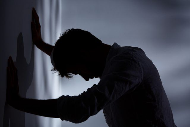Man leaning with hands against wall, dark room.