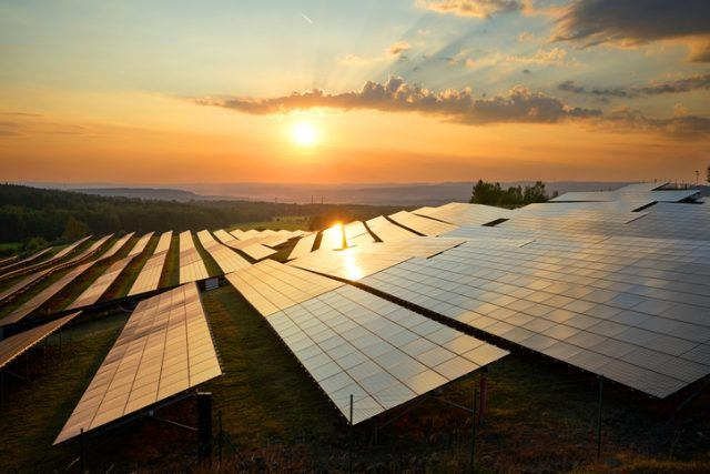 Photovoltaic panels of solar power station in the landscape at sunset.