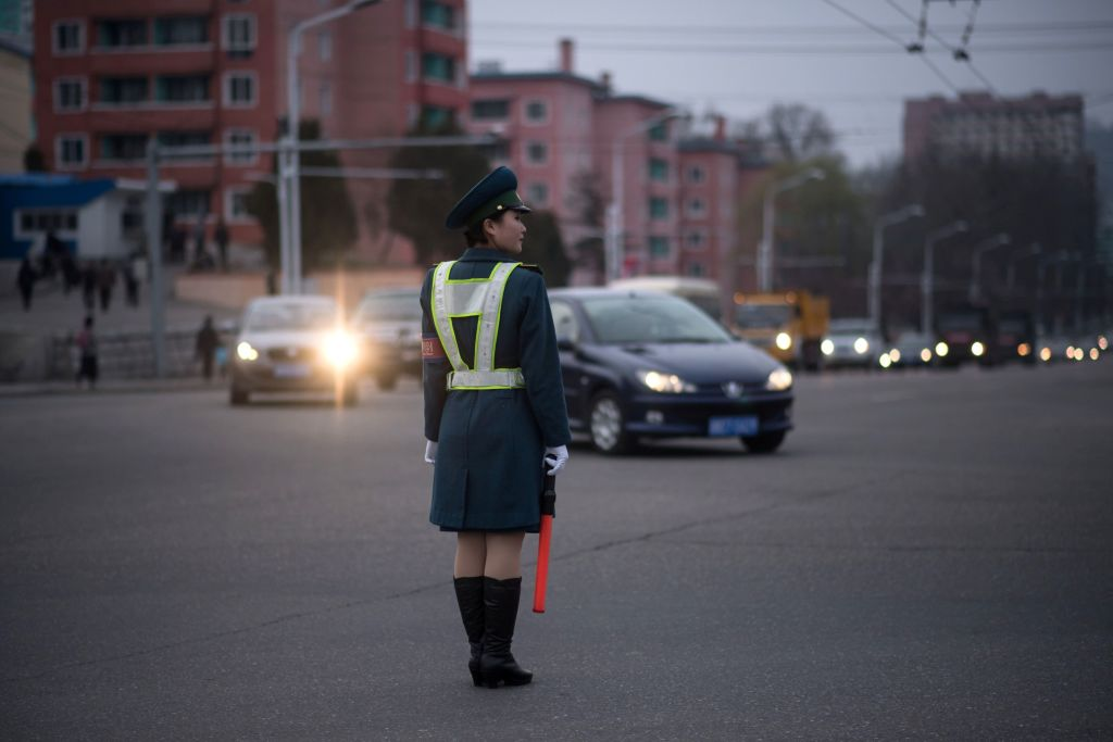 a woman in uniform directs traffic in north korea