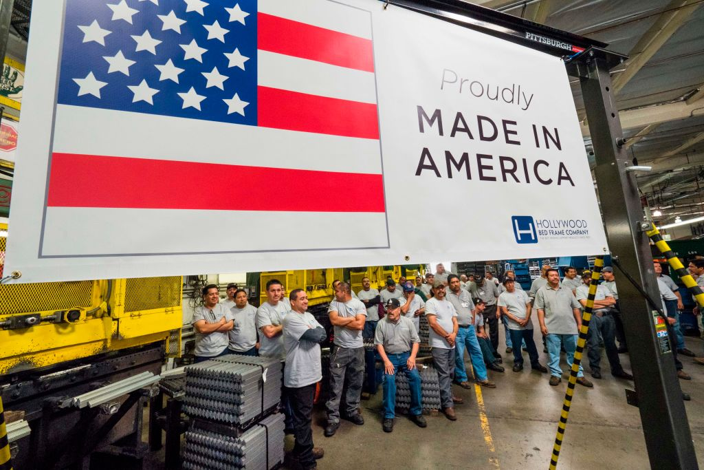 workers at the american bed frame company in front of a made in america sign
