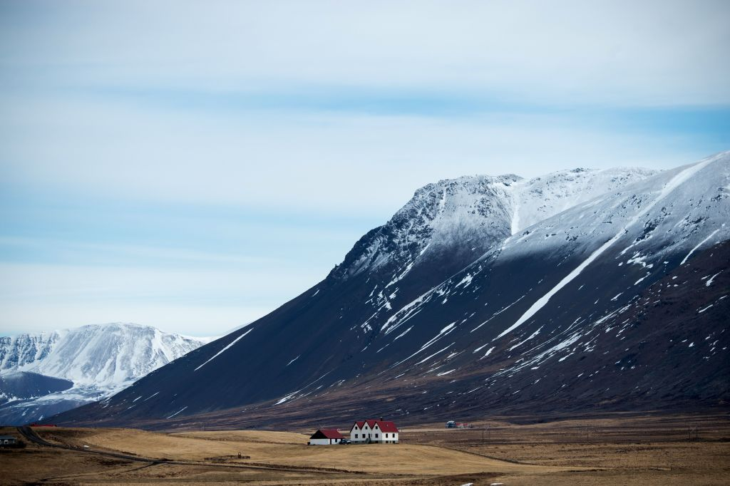 a mountain over a plain with a small house in iceland