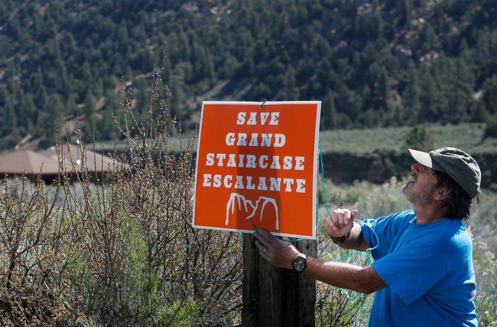 """A man hanging a sign saying """"save grand staircase escalante"""""""