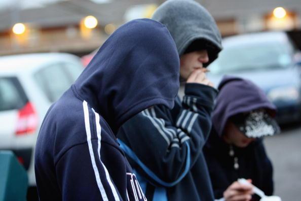 two boys smoking next to cars wearing navy blue hoodies
