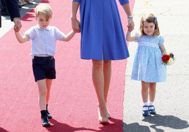 Prince George and Princess Charlotte of Cambridge walking with Kate Middleton.