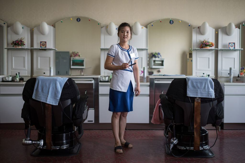 a hairdresser poses in a salon in North Korea