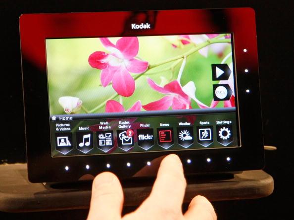 a hand demonstrates a digital photo frame