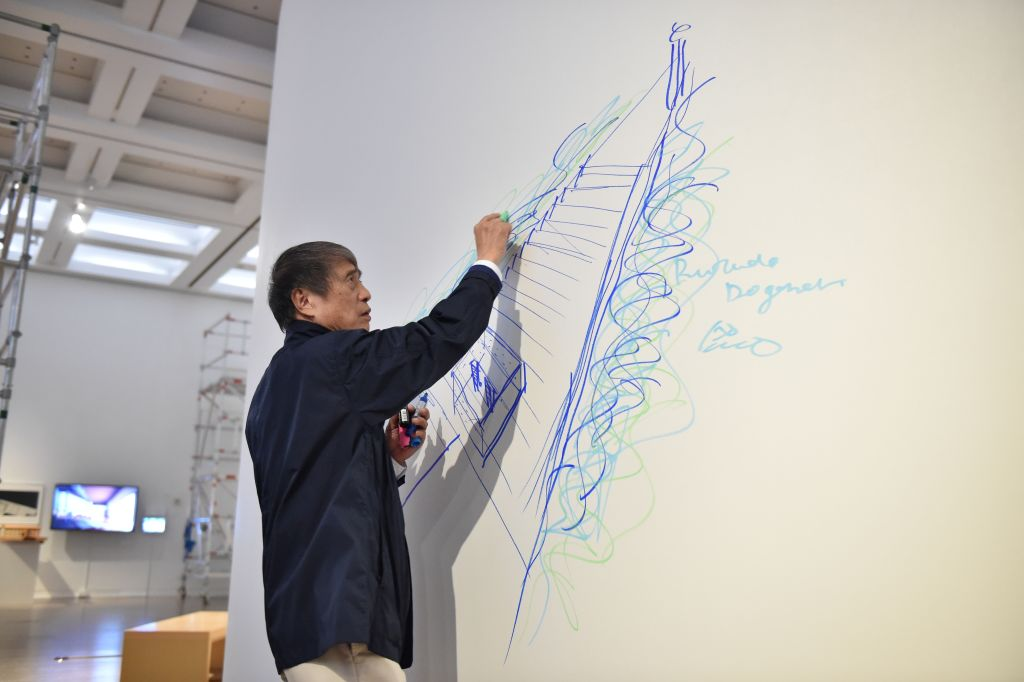 an architect draws with blue marker on a large white piece of paper in an artspace in japan