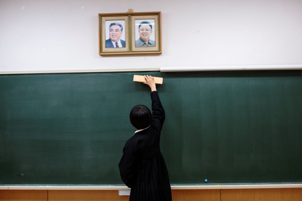A student cleans the blackboard under portraits of late North Korean leaders Kim Il Sung and Kim Jong Il.